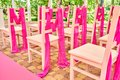 Wedding chairs on each side of archway. Place for wedding ceremony decorated in pink color, wooden chairs for guests outdoors. Royalty Free Stock Photo