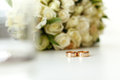 Wedding composition of wedding rings on blurred background bouquet of white roses Royalty Free Stock Photo