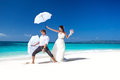Wedding couple on beach having fun bride and groom the with umbrellas tropical Royalty Free Stock Photography