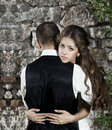 Wedding couple bride embracing groom over stone brick wall Stock Image