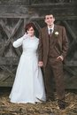 Wedding couple bride and groom dressed in vintage dress and suit holding hands and smiling with wooden door behind them Stock Photography