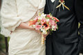 Wedding couple with brides bouquet torsos from orange calla lilies and freesia selective focus on a Stock Photos