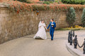Wedding couple, cheerful bride and loving groom strolling in park near sandstone wall Royalty Free Stock Photo