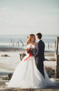 Wedding couple groom bride with bouquet posing near sea on sunset Stock Images