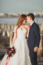 Wedding couple groom bride with bouquet posing near sea on sunset Royalty Free Stock Image