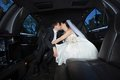 Wedding couple kissing each other newlywed in limousine Stock Photography