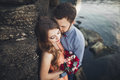 Wedding couple kissing and hugging on rocks near blue sea Royalty Free Stock Photo