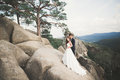 Wedding couple in love kissing and hugging near rocks on beautiful landscape