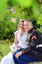 Wedding couple in park a military on a bench a through the trees Royalty Free Stock Image
