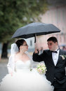 Wedding couple in rain walking with umbrella Royalty Free Stock Photography