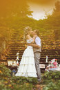Wedding couple in a rustic style kissing near the stone steps surrounded by wedding decor at autumn forest Royalty Free Stock Photo