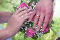 Wedding couple showing rings a newly wed place their hands on a bouquet Royalty Free Stock Images
