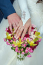Wedding couple showing rings a newly wed place their hands on a bouquet off their bands Royalty Free Stock Photo
