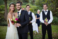 Wedding couple standing with bouquet of flowers in garden Royalty Free Stock Photo