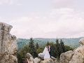 Wedding couple standing at rocky mountains against the sky and embracing. Cute romantic moment. Royalty Free Stock Photo