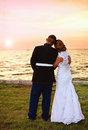 Wedding couple at sunset a back view of bride and military groom watching outside after Royalty Free Stock Image