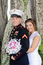 Wedding couple three quarter portrait of a bride and military groom holding a bouquet of flowers Stock Image