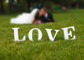 Wedding couple unfocused and love word on the grass Royalty Free Stock Photo
