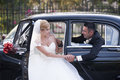 Wedding couple with a vintage car in looking each other Stock Image