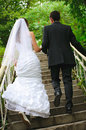 Wedding couple walk up to stairs and holding hands backview run Royalty Free Stock Photo