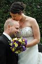 Wedding day bride gives a tender kiss on the bald head of her man Royalty Free Stock Images