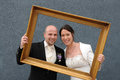 Wedding day bride and groom in a golden picture frame Royalty Free Stock Photos