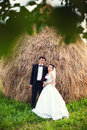 Wedding day portrait of groom and bride outdoors in countryside near a hay stack Stock Photo