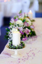 Wedding decor table setting and flowers with candle focused to candle Royalty Free Stock Images