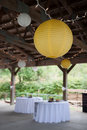 Wedding decorations reception in a pavilion setting with lights hanging from ceiling and table cloths Royalty Free Stock Images