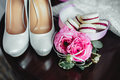 Wedding details, decoration. Bouquet of pink roses, bridal accessories and macaroons stand on a wooden table. Soft focus Royalty Free Stock Photo