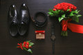 Wedding details. Groom accessories. Shoes, rings, belt, boutonniere and watch on table. Royalty Free Stock Photo