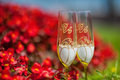Wedding goblets among red flowers Stock Photo