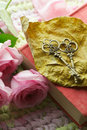 Wedding guest book two old vintage keys with a heart shape lying on an autumn leaf surrounded by pretty roses symbol of long Royalty Free Stock Photo