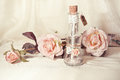 Wedding invitation in a glass bottle and pink roses Royalty Free Stock Photo