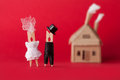 Wedding invitation and love concept. Bride groom clothespin peg characters, cardboard home on red background. Abstract Royalty Free Stock Photo