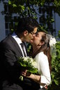 Wedding kiss of a young hispanic couple portrait bride and groom kissing each other just married newly weds Royalty Free Stock Images