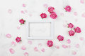 Wedding mockup with white frame, pink rose flowers and petals on light table top view. Beautiful floral pattern. Flat lay style. Royalty Free Stock Photo