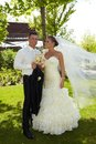 Wedding photo of happy couple full length outdoor young on day embracing bride wearing long veil Stock Photo