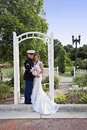Wedding portrait in park a happy military groom uniform holding his bride under an arch a Stock Photos
