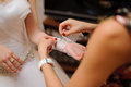 Wedding preparation bridesmaid with red nails helping bride to put on glove Royalty Free Stock Photography