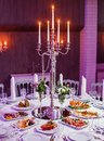 Wedding reception dinner. Round table served with flowers, shiny candles and appetizer food. Holiday banquet menu Royalty Free Stock Photo