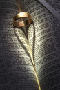 Wedding ring heart shadow a on an open bible casting a shaped Stock Photography
