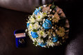 Wedding rings in a blue box a bridal bouquet of white flowers and blue roses on background temnof preparing for the Royalty Free Stock Photos