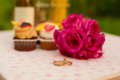 Wedding rings and bouquet accessories on the table rose cakes drink Royalty Free Stock Photos