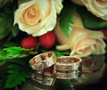 Wedding rings with bouquet focus on the rings golden Stock Photo