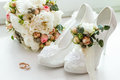 Wedding rings, boutonniere, bouquet and bridesmaid shoes. Royalty Free Stock Photo