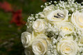 Wedding rings on bridal bouquet golden with gentle white roses Stock Image