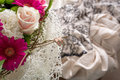 Wedding rings and bridal bouquet high angle of bride groom hanging on twigs of with gown in background a traditional symbol of Royalty Free Stock Photo