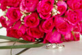 Wedding rings and bridal bouquet over whi of pink roses white Royalty Free Stock Photography