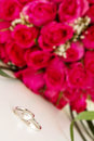 Wedding rings and bridal bouquet over whi of pink roses white Royalty Free Stock Photos